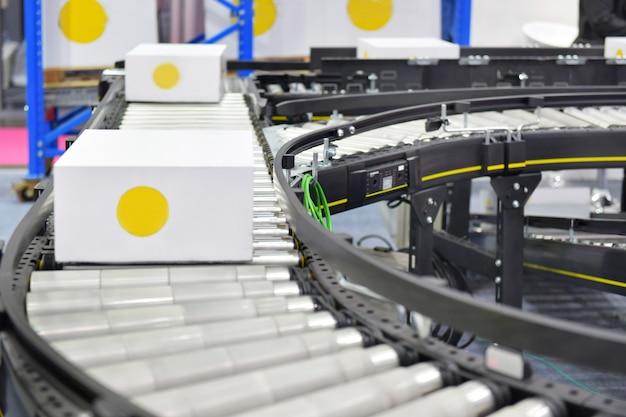Kartondozen op transportband het concept van het het vervoerssysteem van tarieven