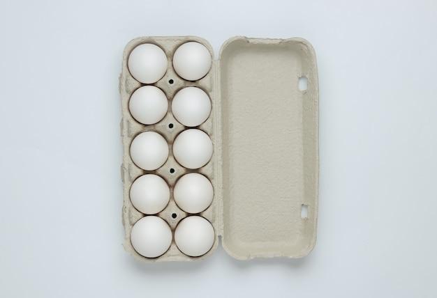Kartonnen bakje met eieren op een witte achtergrond