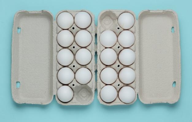 Kartonnen bakjes met eieren op blauwe pastel achtergrond minimalisme kookconcept