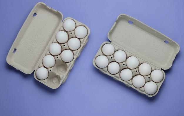 Kartonnen bakjes met eieren op paarse pastel achtergrond