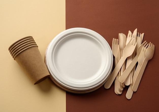 Kartonnen beker en houten vork, leeg rond bruin wegwerpbordje gemaakt van gerecycled materiaal op een bruine ondergrond. concept van de afwezigheid van niet-recyclebaar afval, afwijzing van plastic, bovenaanzicht