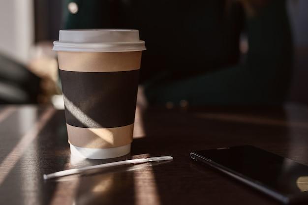 Kartonnen beker met koffie, cappuccino, latte, thee en smartphone op houten tafel in café in felle zonnestralen