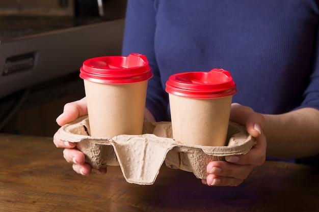 Kartonnen bekers met cappuccino in een afhaalkraam in de handen van een vrouw