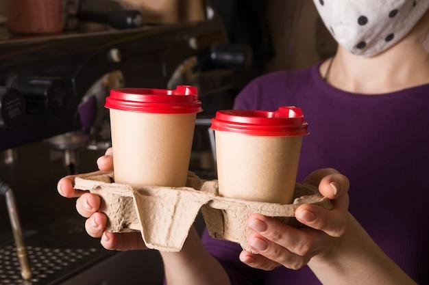 Kartonnen bekers met cappuccino in een afhaalstandaard in de handen van een vrouw met gezichtsmasker