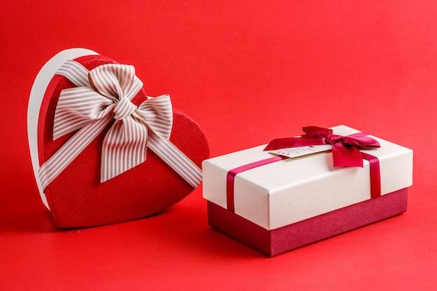 Kartonnen biologisch afbreekbare geschenkdoos in de vorm van een hart en in de vorm van een rechthoek met rode strikken