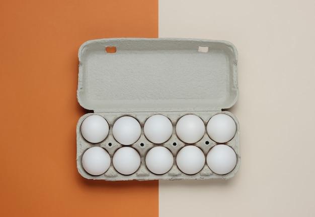 Kartonnen dienblad met eieren op bruin beige achtergrond