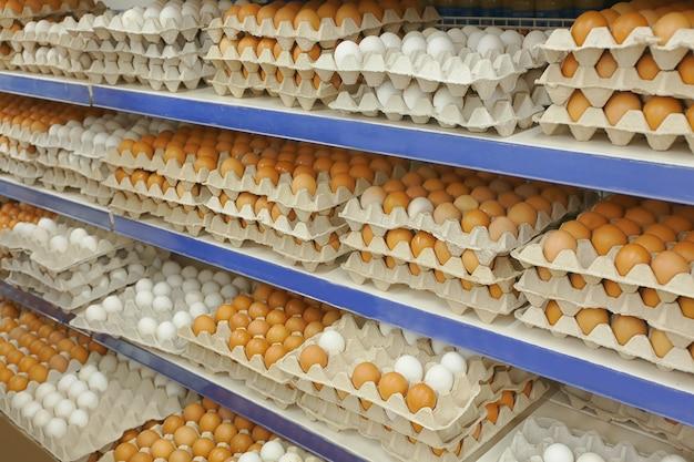 Kartonnen dienbladen met kippeneieren op planken bij supermarkt