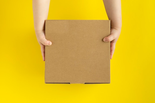 Kartonnen doos in de handen van kinderen op gele achtergrond