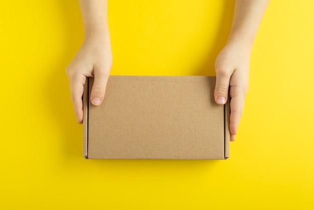 Kartonnen doos in handen van het kind op gele achtergrond, bovenaanzicht.