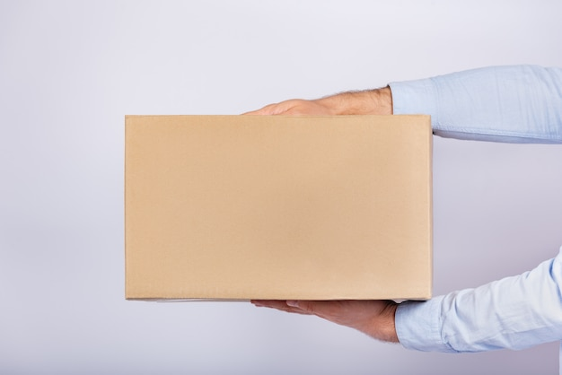 Kartonnen doos in mannelijke handen. pakketbezorging thuis. geschenk