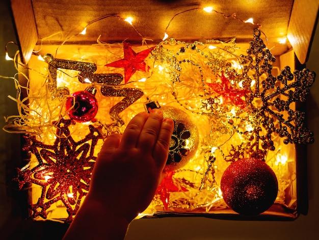 Kartonnen doos kerstversiering en gloeilampen. kleine baby gouden sprankelende bal bloem aan te raken.