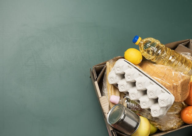 Kartonnen doos met diverse producten, fruit, pasta, zonnebloemolie in een plastic fles en conservering. donatie concept, bovenaanzicht