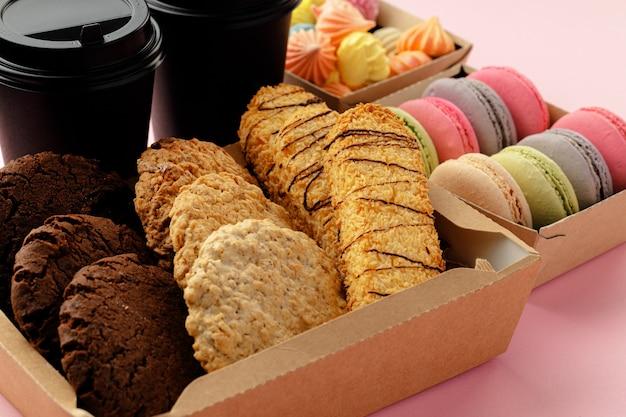 Kartonnen doos met haverkoekjes op roze tafel