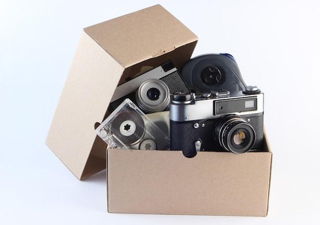 Kartonnen doos met retro filmcamera, audiocassette, gamepad op een wit