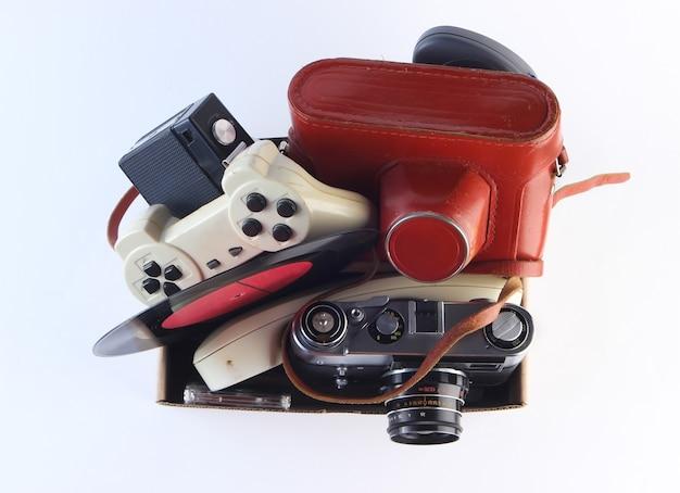 Kartonnen doos met retro filmcamera, gamepad, vinylplaat, telefoonslang op een wit