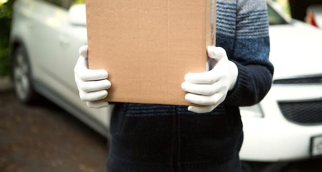 Kartonnen doos met ruimte voor tekst in de handen van een mannelijke koerier in witte handschoenen. koerier op de achtergrond van een witte auto.