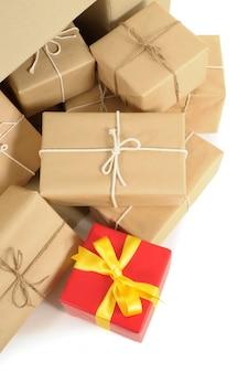 Kartonnen doos met verschillende pakjes bruin papier en één uniek rood geschenk