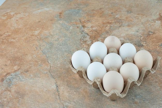 Kartonnen doos met verse witte kippeneieren op marmeren tafel.