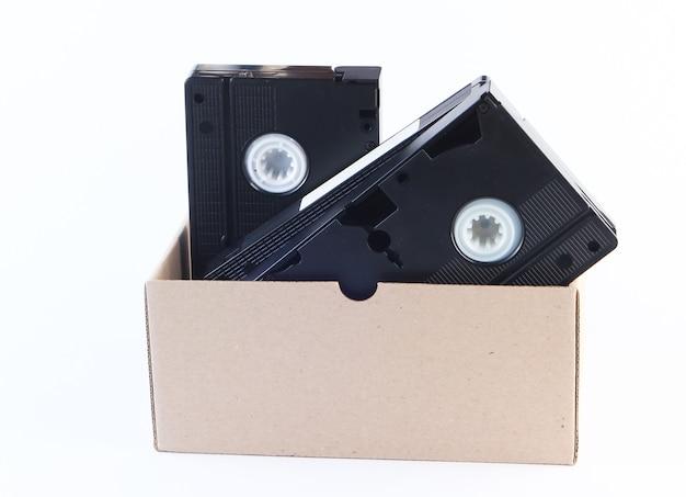 Kartonnen doos met videocassettes op een wit