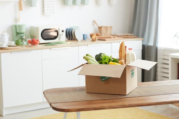 Kartonnen doos met voedsel op houten tafel in minimaal keukeninterieur