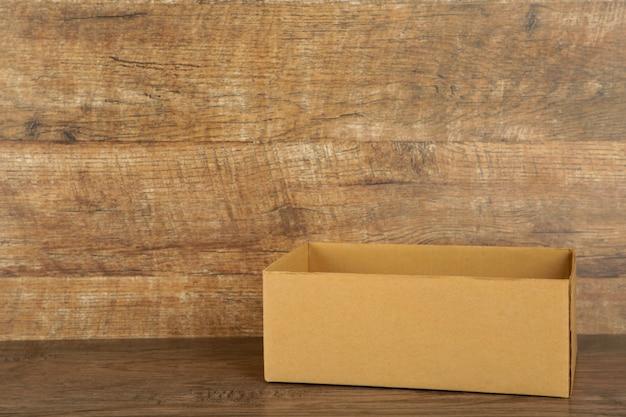 Kartonnen doos op de broun achtergrond. kopieer ruimte
