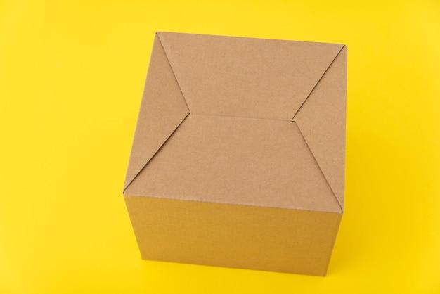 Kartonnen doos op gele achtergrond. ambachtelijke verpakking. achterkant van pakket