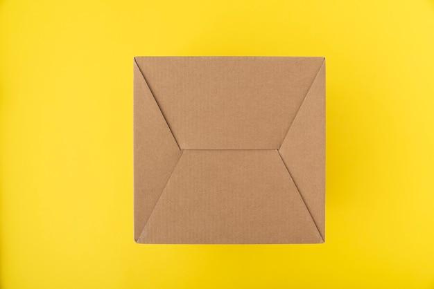 Kartonnen doos op gele achtergrond. ambachtelijke verpakking.