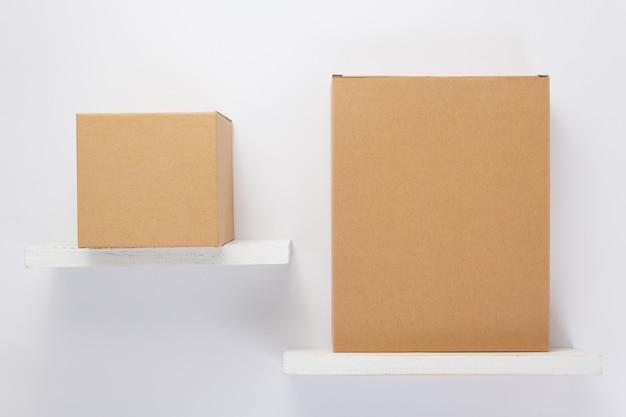 Kartonnen doos op houten plank bij witte achtergrond