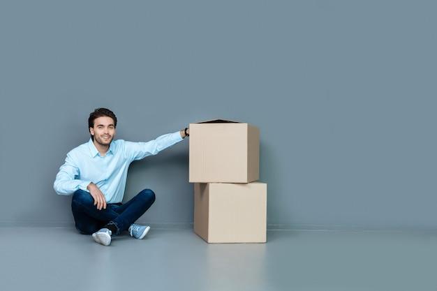 Kartonnen dozen. aardige positief opgetogen man zittend op de vloer en glimlachend terwijl hij zijn hand op kartonnen dozen legde