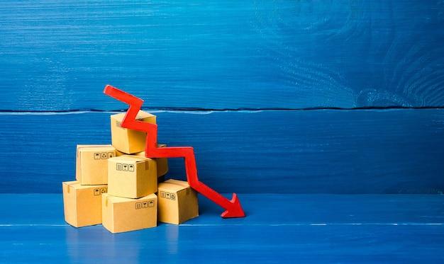 Kartonnen dozen en rode pijl-omlaag. daling van verkoop- en productiegoederen, laag leveringsvolume