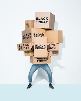 Kartonnen dozen met black friday inscriptie in de handen van een jonge man