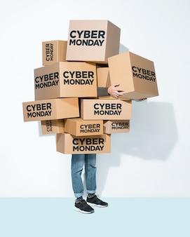 Kartonnen dozen met cyber maandag inscriptie in de handen van een jonge man