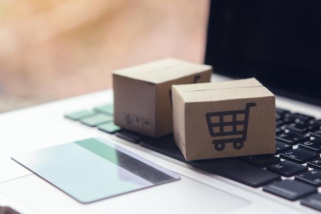 Kartonnen dozen met een winkelwagen logo en creditcard op een laptop toetsenbord.