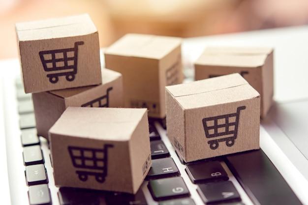 Kartonnen dozen met een winkelwagen-logo op een laptop toetsenbord