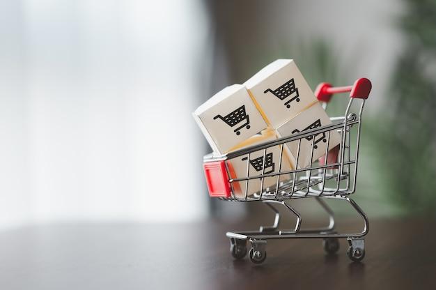 Kartonnen dozen met winkelwagenlogo in een trolley voor bezorging. online winkelen of marketing en commerce concept