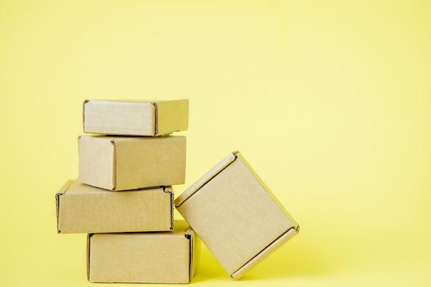 Kartonnen dozen van verschillende grootte op gele achtergrond.