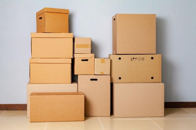Kartonnen dozen voor het bewegen op de vloer tegen grijze muur