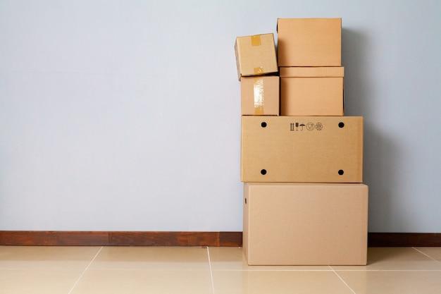 Kartonnen dozen voor het verplaatsen op de vloer tegen grijze muur