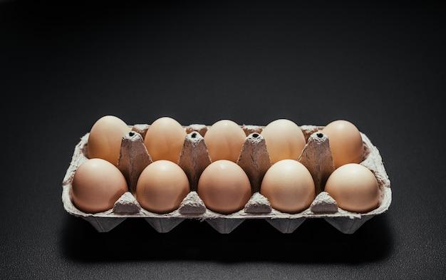 Kartonnen eierdoos op zwarte houten achtergrond.