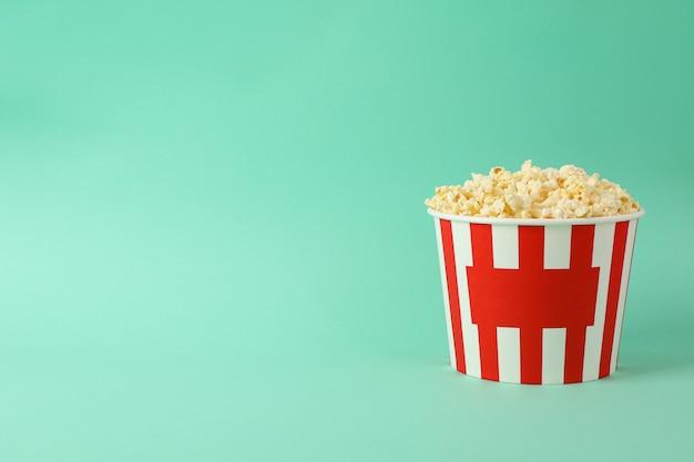 Kartonnen emmer met smakelijke popcorn op mint ruimte