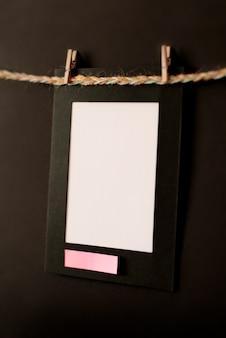 Kartonnen fotolijst en notitie op zwarte achtergrond