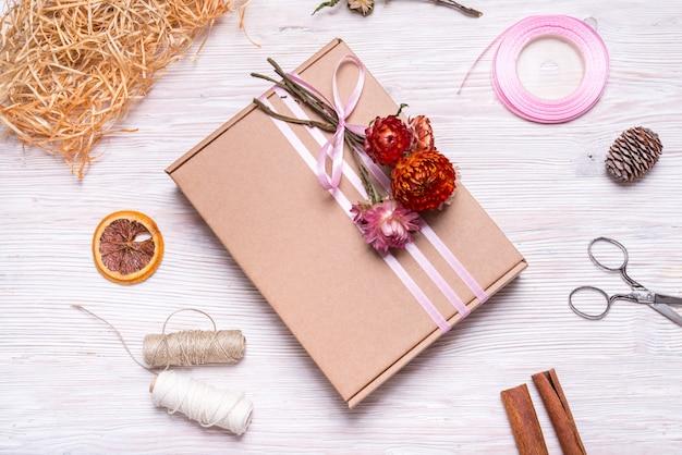 Kartonnen geschenkdoos versierd met gedroogde bloemen op houten tafel