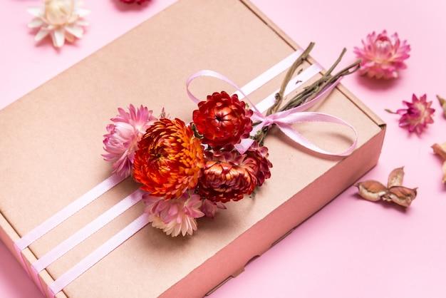 Kartonnen geschenkdoos versierd met gedroogde bloemen op roze tafel