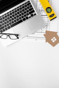 Kartonnen huis met waterpas en laptop