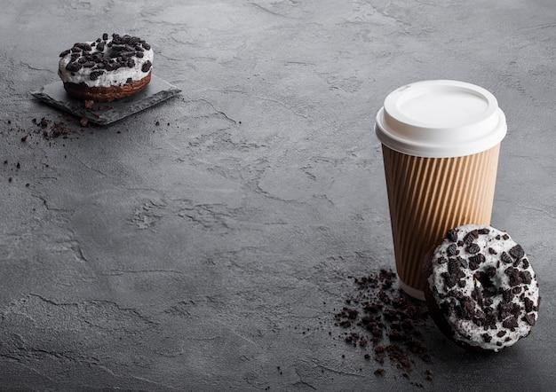 Kartonnen koffiekopje met zwarte koekjes donuts op zwarte stenen keukentafel. cafe drankje en snack.
