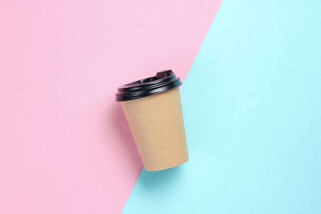Kartonnen koffiekopje op blauw roze. bovenaanzicht