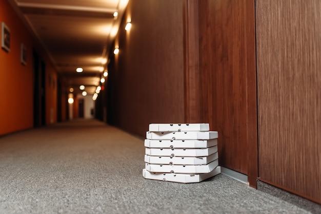Kartonnen pizzadozen bij de deur.
