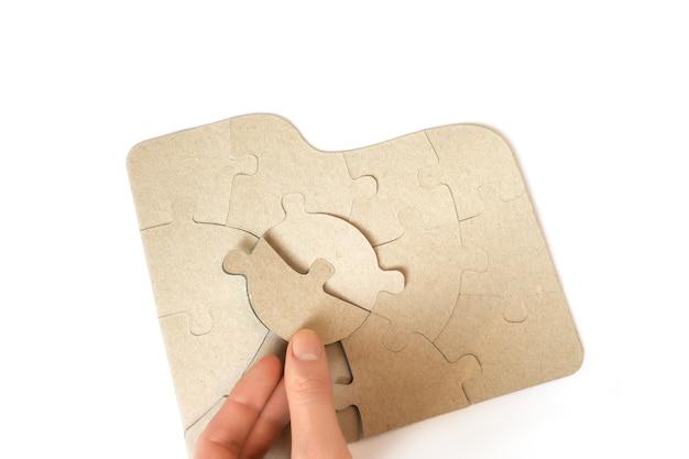 Kartonnen puzzels in vrouwelijke handen, close-up.