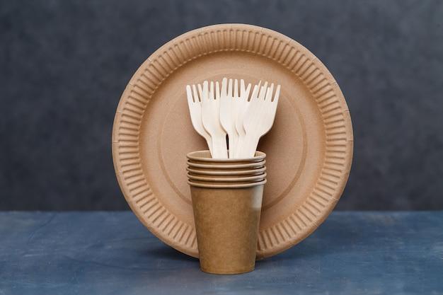 Kartonnen wegwerpschalen gemaakt van milieuvriendelijke materialen. verstopt de natuur niet milieuvriendelijke, wegwerpbare, recyclebare, composteerbare schalen. papieren bekers om te drinken, borden