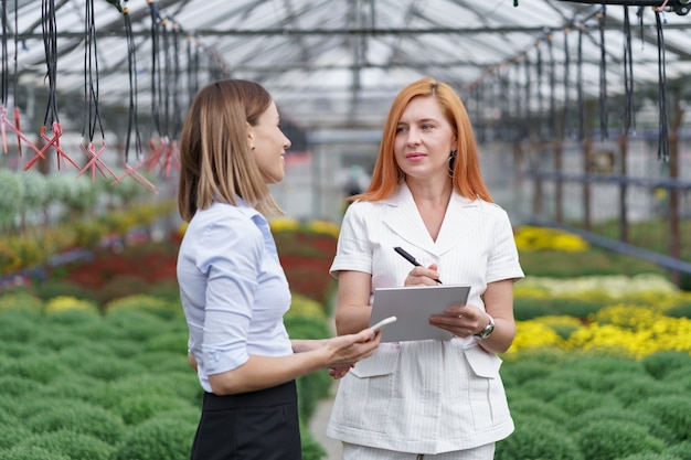 Kaseigenaar presenteert bloemenopties aan een potentiële klantendetailhandelaar.